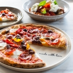 Diavolo pizza with wood-roasted peppers, hot salami & olives